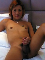 Short-haired Ladyboy plays with dick in bed